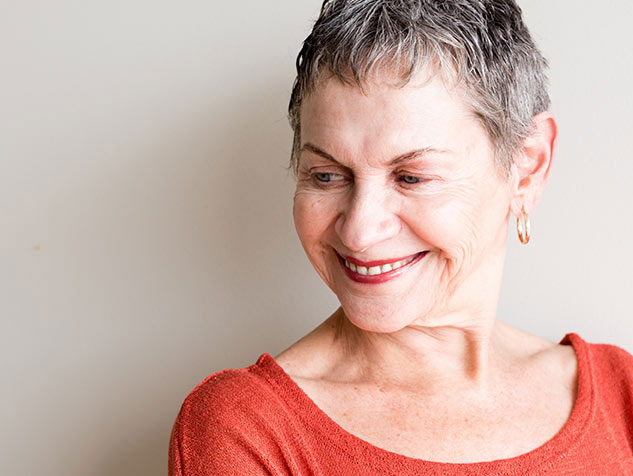 older woman with dental implants smiling