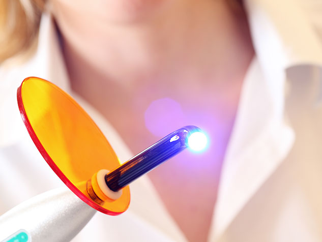 dentist holding kerning light for fillings