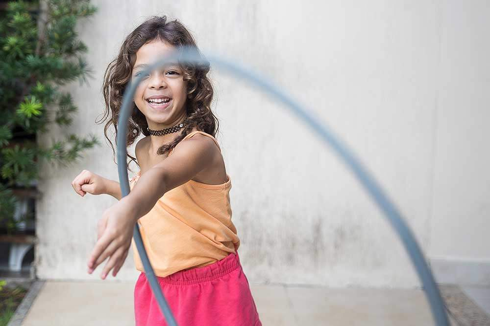 young girl playing with hoola hoop outside